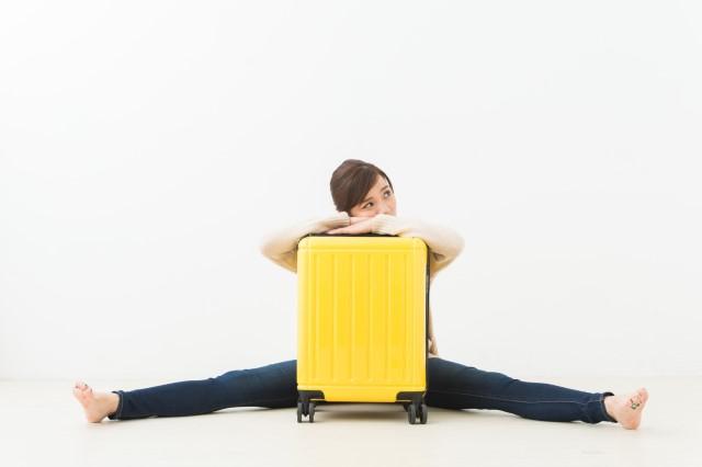 スーツケースが重くて困っている女性のイメージ画像