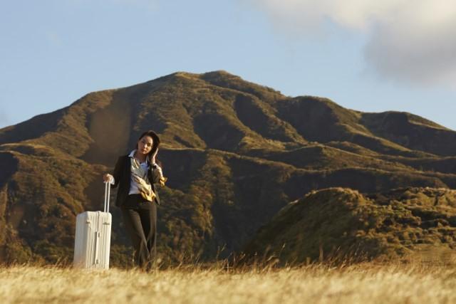 夢の中でスーツケースを持って海外旅行をしている女性のイメージ画像