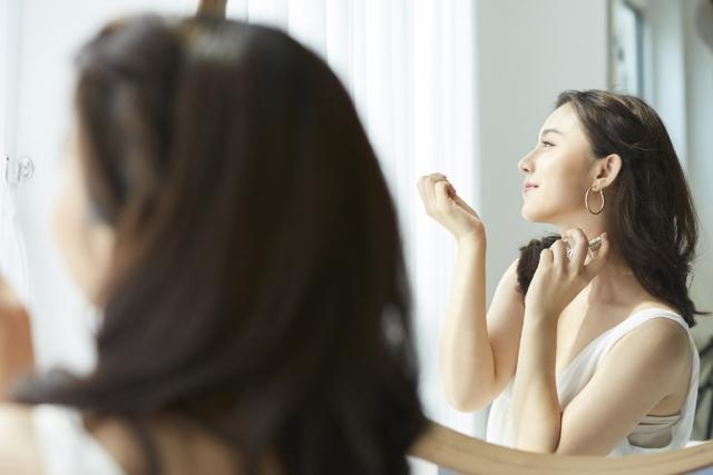 香水を使う願いが叶うおまじないを試している女性のイメージ画像