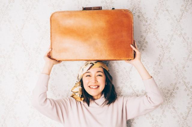 スーツケースを持って喜んでいる女性の画像