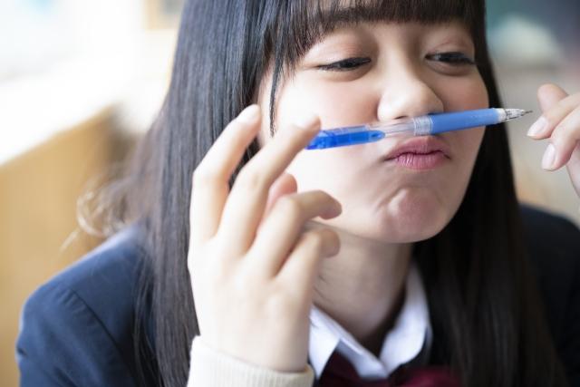 シャーペンを使う恋愛の願いが叶うおまじないをしている女子校生のイメージ画像