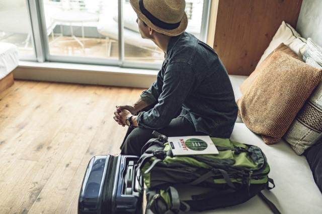 旅行に行くのが憂鬱そうな男性のイメージ画像