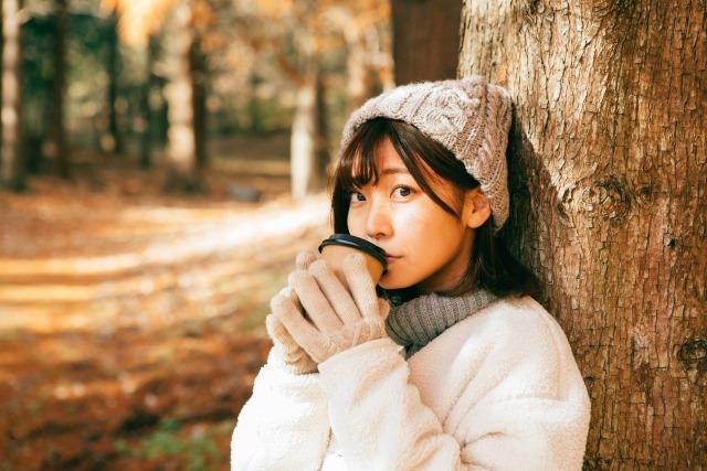 手袋をしてホットコーヒーを飲んでいる女性のイメージ画像